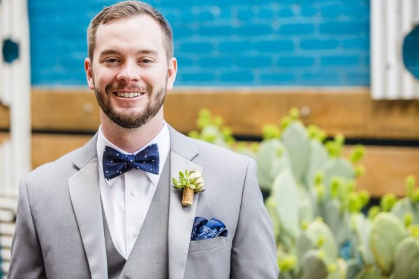 Groom with wine cork and succulent boutonniere. Caitlin & Ryan Photography.