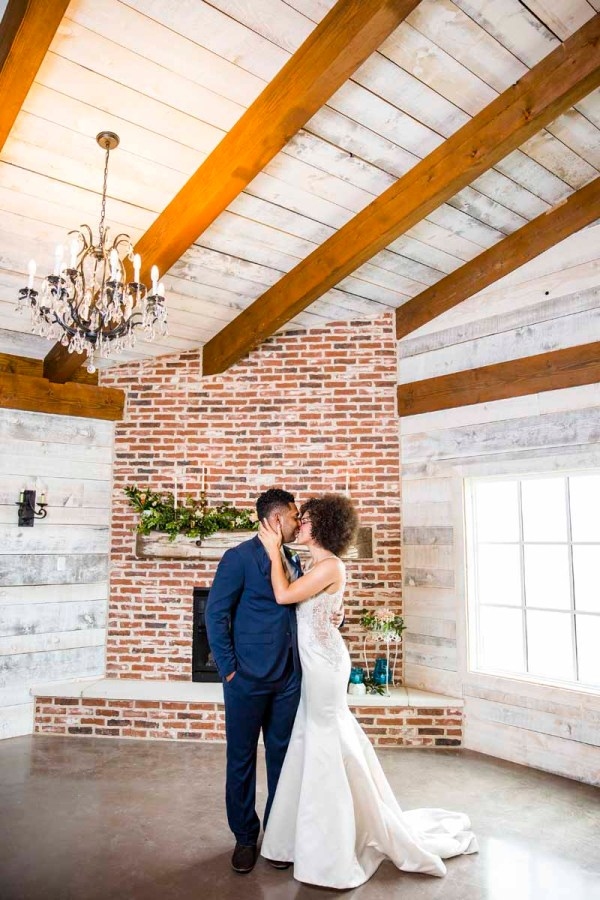 Bride and groom in front of Eberley Brooks' stunning fireplace. Texas wedding planner Jessica Ormond Events. Caitlin and Ryan Photography.
