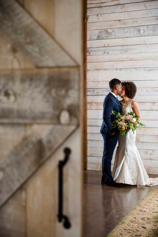 bride and groom seen through barn door Eberley Brooks Events in West Texas. Jessica Ormond Events. Caitlin and Ryan Photography.