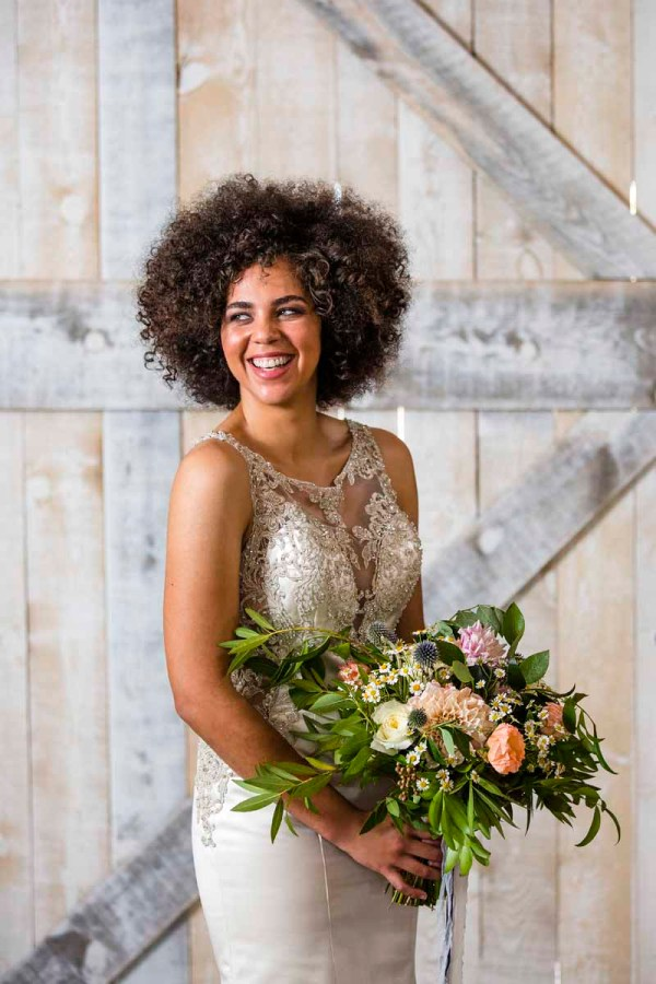 Smiling bride with bouquet of dahlia, poppies, thistle, and chamomile made by Lubbock florist Jessica Ormond Events for Texas style shoot by Caitlin and Ryan Photography at Eberley Brooks Events.