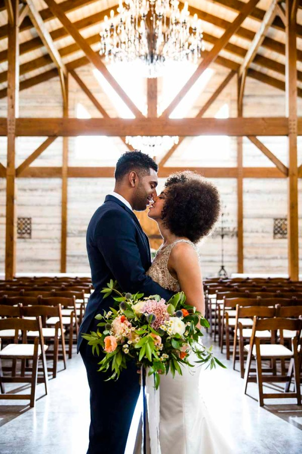 Bride and groom at Barn ceremony with garden bouquet. West Texas wedding florist Jessica Ormond Events. Caitlin and Ryan Photography.