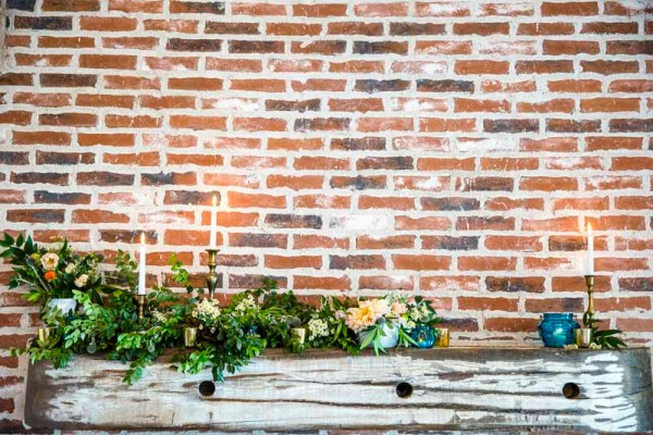 Eberley Brooks Events fireplace mantel covered in wild greens and candles. Designed by West Texas wedding florist Jessica Ormond Events. Caitlin and Ryan Photography.