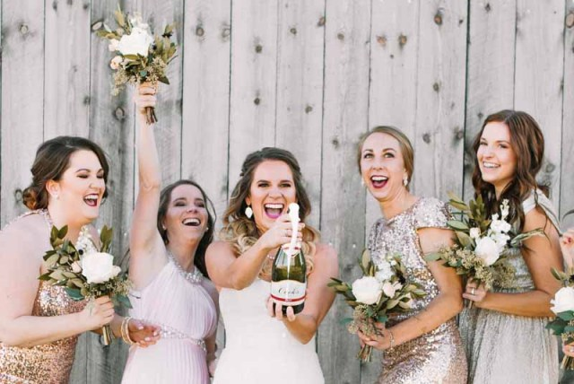 Bride and bridesmaid sharing champagne at Eberley Brooks Event Center in Lubbock Texas. Ashley J Photography. Bouquets by florist Jessica Ormond Events. Image by Ashley J Photograhpy.