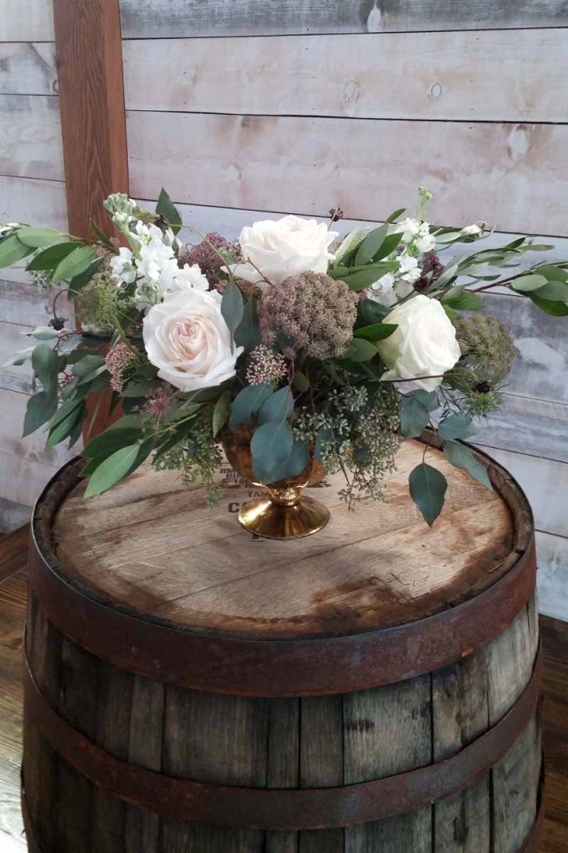 Alter arrangement of greenery and garden roses on a wine barrel at Eberley Brooks Event Center in Lubbock Texas. Designed by Jessica Ormond Events West Texas wedding florist.