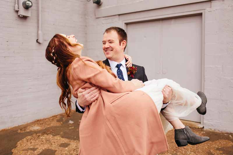 Groom carrying laughing bride. Urban winter wedding. Texas wedding designer Jessica Ormond Events. Photo by Betsy.