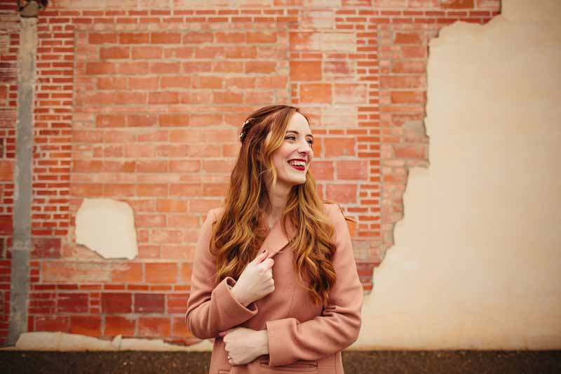 Beautiful red head bride by distressed brick wall. Downtown Lubbock winter wedding. Wedding designer Jessica Ormond Events. Photo by Betsy.