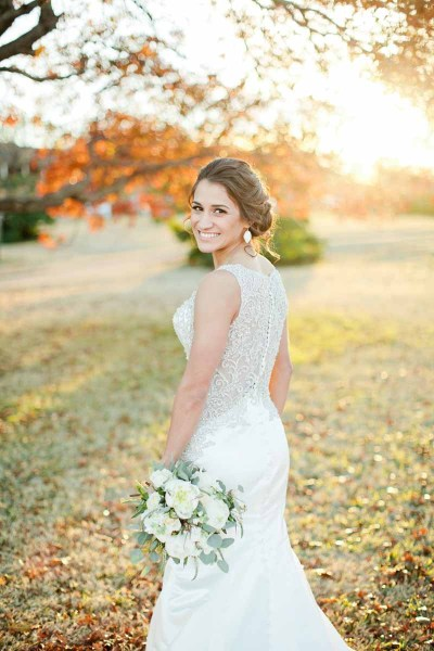 Bride in West Texas sunset holding a white peony and eucalyptus bouquet. Bridal bouquet designed by Lubbock florist Jessica Ormond Events. Image by Tara Hobgood Photography.