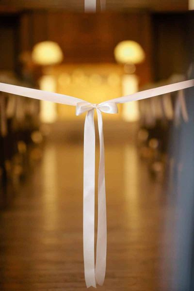 Elegantly tied ribbon on the Legacy Event Center aisle for a winter wedding. Lubbock florist Jessica Ormond Events. Wedding photograher Tara Hobgood.