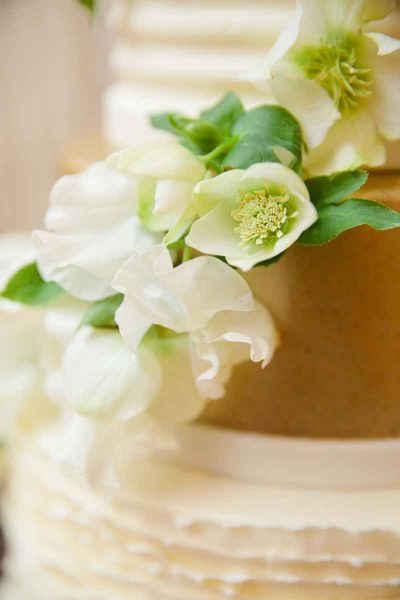 Gold and white wedding cake with Sweet Pea and Hellebore flowers at the Legacy Event Center in Lubbock. Tara Hobgood Photography