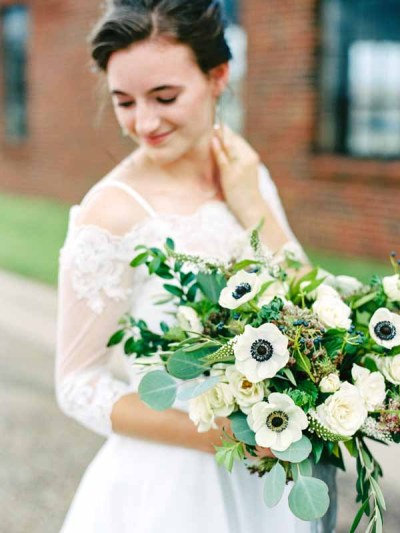 Classic bride in lace gown with organic bouquet featuring white anemones. Bouquet designed by Texas florist Jessica Ormond Events. Photo by Katie Rivera Photography.