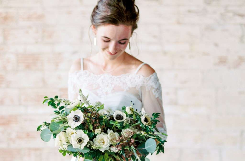 Bride in front of brick wall with anemone bouquet by Jessica Ormond Events
