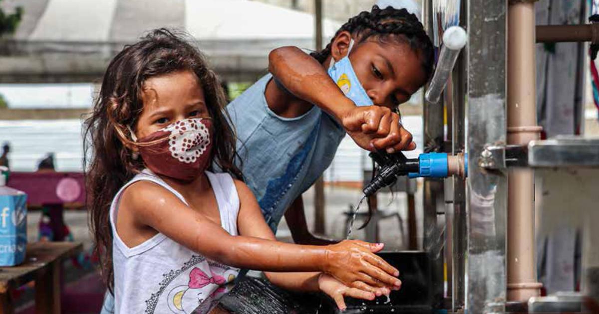Refugiados venezuelanos e migrantes lavando as mãos antes de participar do abertura de um abrigo para vulneráveis Venezuelanos em Boa Vista - foto:  ACNUR / LUCAS NOVAES