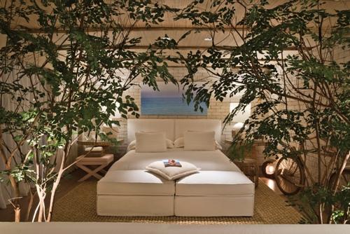 planta no quarto, cama branca com cabaceira branca, banquinho em x, parede de tijolinho branco aparente, almofada branca, tapete fibra natural clara