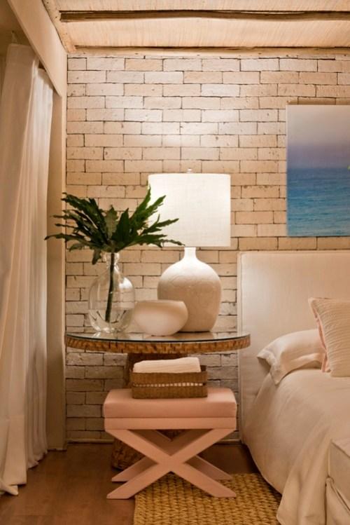 quarto, cama cabeceira de linho branca, mesa lateral com abajur branco e parede de tijolinho branco aparente