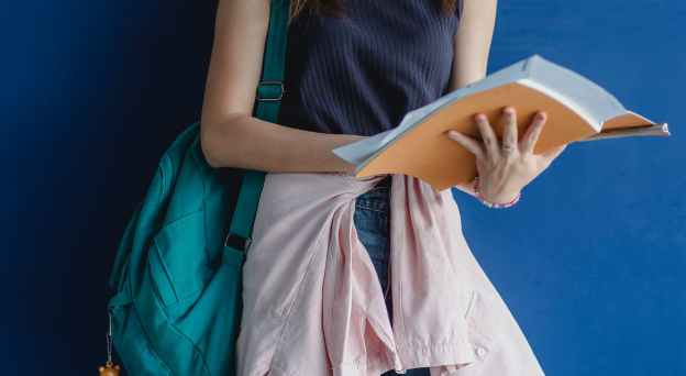 faceless female student standing with notebook