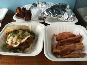 Clockwise from left: 1) Organic pork belly confit and free-range egg sandwich with spinach, yolks, and honey dijon, 2) truffle potato skewers, 3) extra bacon.