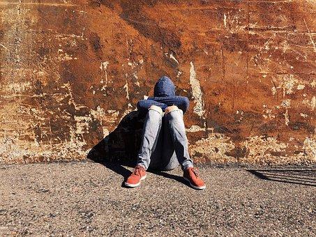 joven sentado en la calle, apoyado contra la pared con la cabeza hundida entre los brazos apoyados cobre las piernas.
