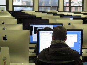 salon de capacitación con computadoras y algunas personas trabajando