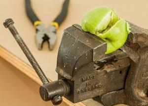 una manzana verde reventada por la presión de un tornillo de banco en la que se encuentra