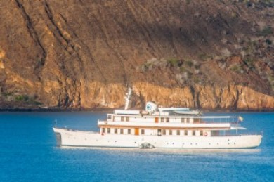 The M/Y Grace at anchor against the vivid backdrop of Bartolomé's red lava cliffs.