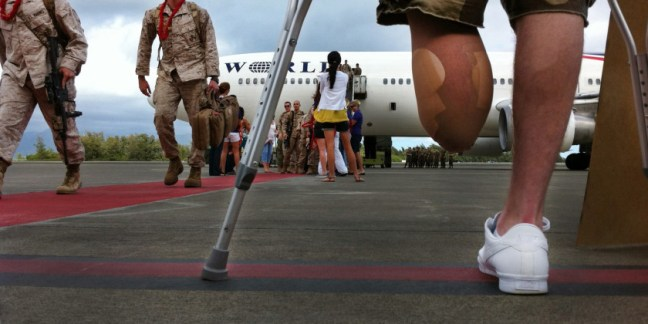 Cpl. Murphy Houston, a Marine amputee with Wounded Warrior Battalion East - Detachment Bethesda, stands on crutches welcoming home Marines of 1st Battalion, 12th Marine Regiment, upon their return from a seven-month deployment to Afghanistan's Helmand province on Nov. 24. Houston was deployed and served with 1/12 when he was injured earlier this year and he and other injured Marines flew from the Bethesda, Md., to see his unit return to Marine Corps Base Hawaii. Hundreds of Marines from 1/12 and 1st Battalion, 3rd Marine Regiment, returned on flights together and the last flight reunited with families at MCB Hawaii on Thanksgiving morning.