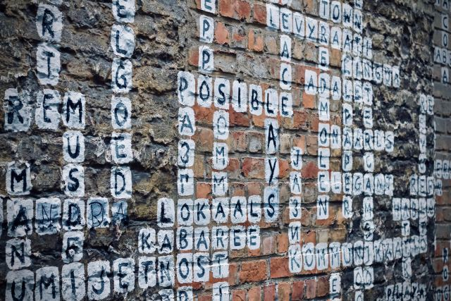 scrabble game drawn in chalk on brick wall