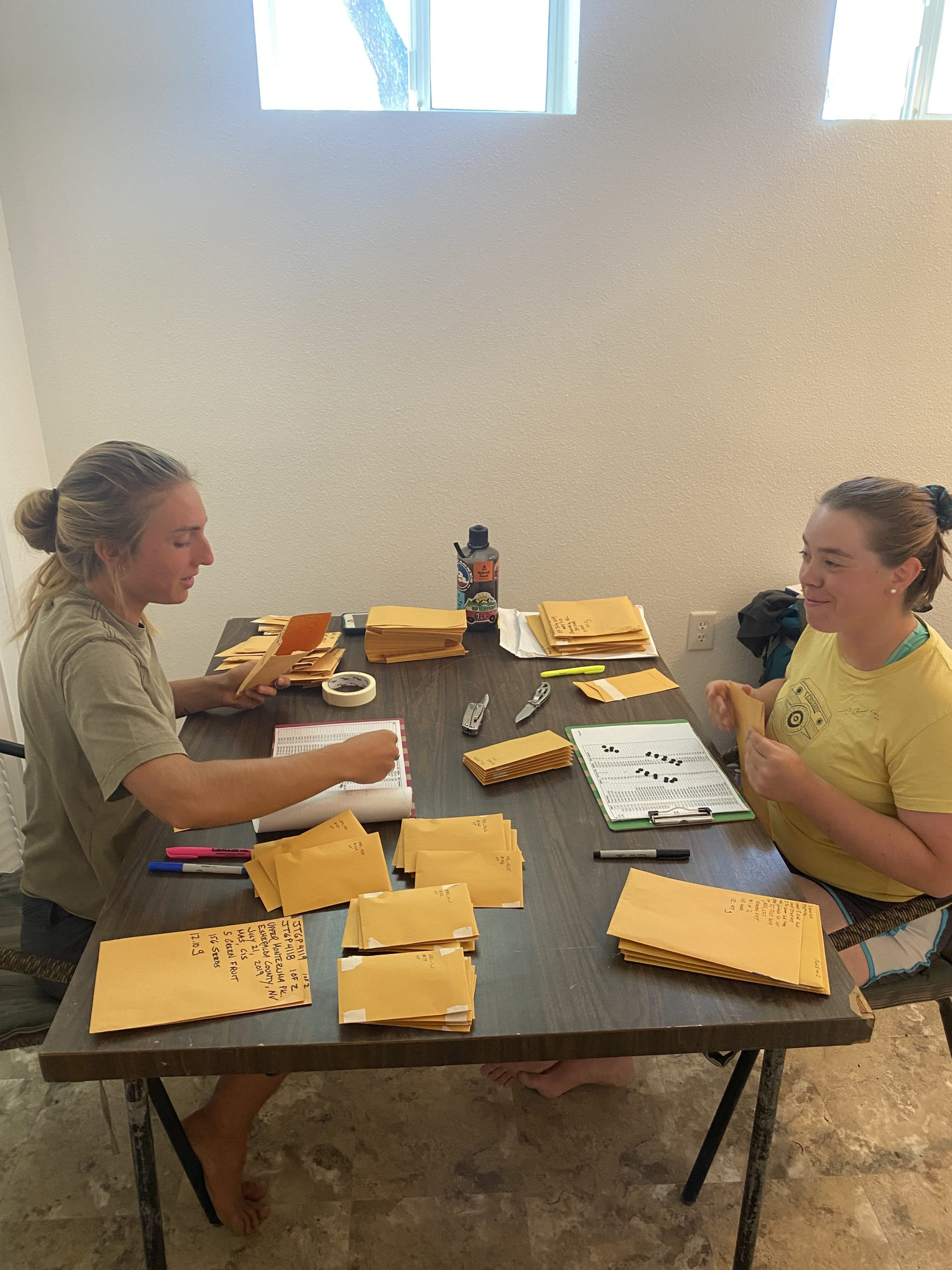 Two young women sit across from each other at a table covered in envelopes and Joshua tree fruits