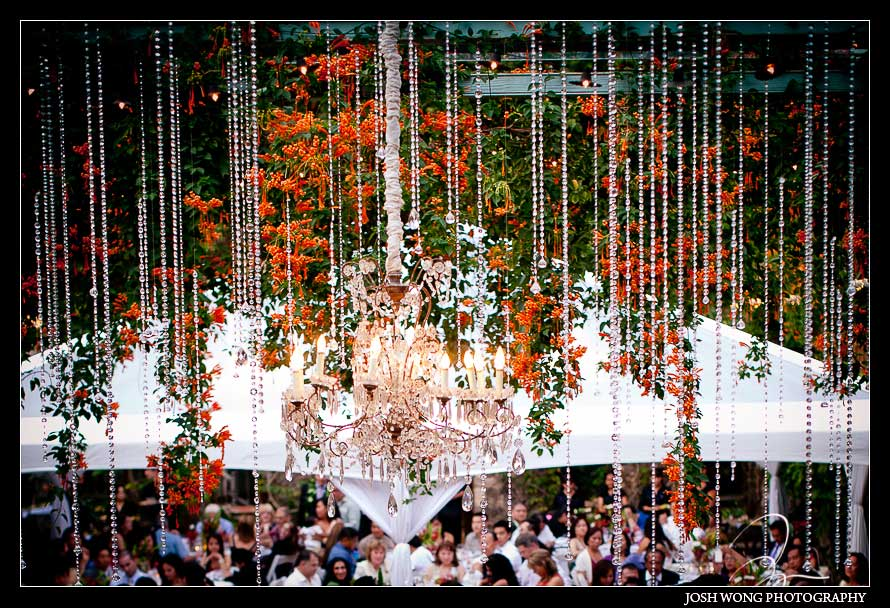 Elaborate crystal chandeliers hang from open air ceiling of Haiku Mill. Haiku Mill Destination Wedding, Maui Hawaii - Wedding Pictures by Destination Wedding Photographer Josh Wong Photography