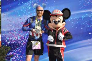 Josh Zeigler presenting his medals with Mickey Mouse at the 2018 Disney World Marathon