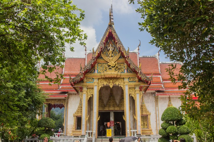 A beautiful golden Thai temple with red tiles reflecting the sun