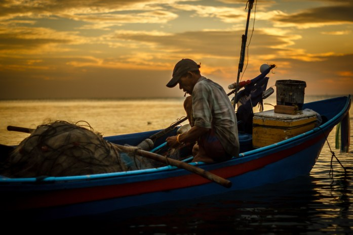 A Thailand fisherman sits on a boat and untangles his fishing nets at sunrise.