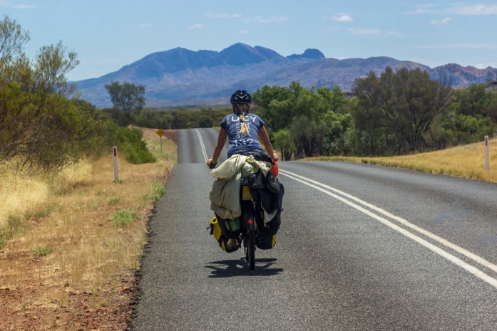Bike tourer cycling on empty road to Mount Sonder in West MacDonnells Mountains in Australia.