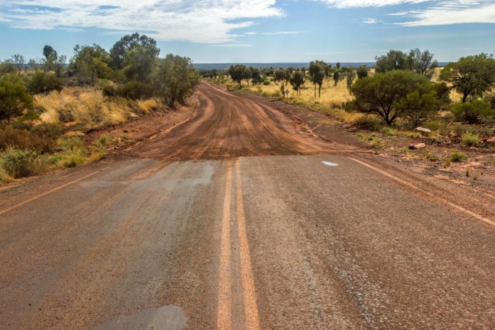 Dirt road meets sealed road in Australian Outback
