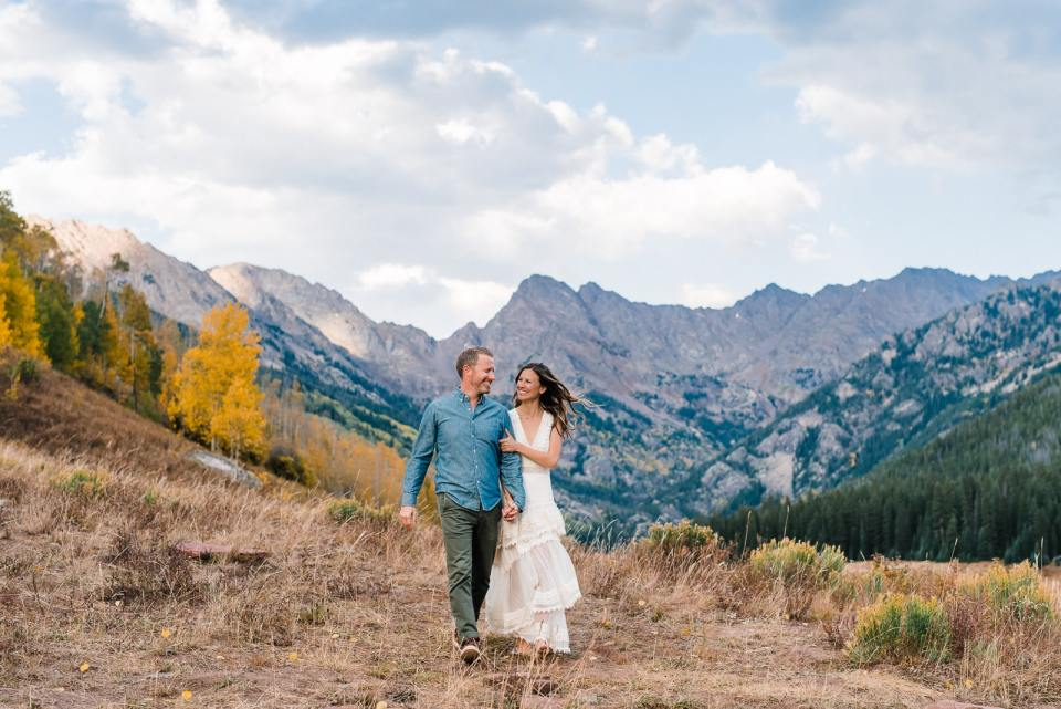 Engaged couple walks at Piney River Ranch for their engagement photo. The stunning mountain range behind Piney Lake makes this one of the best spots in Colorado for engagement photos. There is also a yellow aspen grove at Piney River Ranch that makes this location pop for fall engagement photos.