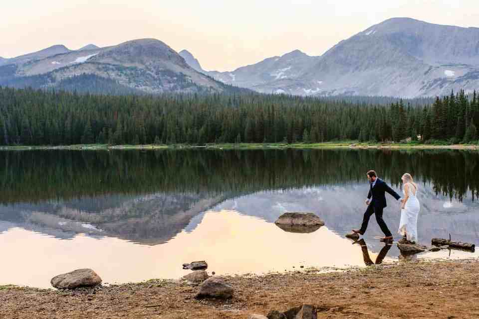 Adventurous Colorado Elopement Inspiration by Josie V Photography. How do you decide between an elopement vs a wedding? Here a couple hikes into the water for their adventurous Colorado elopement. This mountain lake is backdropped by the Rocky Mountains of Colorado, creating a perfect reflection and stunning elopement inspiration.
