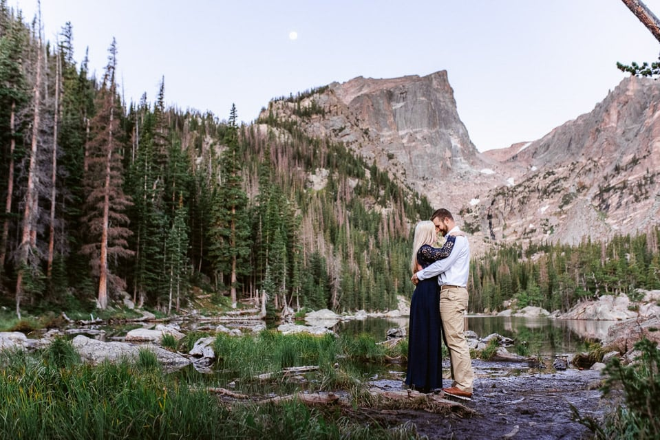 Couple embraces for their engagement photos at Dream Lake in Rocky Mountain National Park. Rocky Mountain National Park is one of the best locations for engagement photos near Denver.