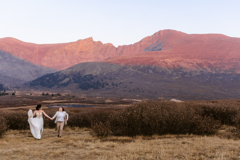 Lesbian elopement photos on top of a Colorado mountain at sunset during the fall. Lesbian couple went with an elopement vs a wedding. Together they run through the fields on top of a mountain pass in Colorado.
