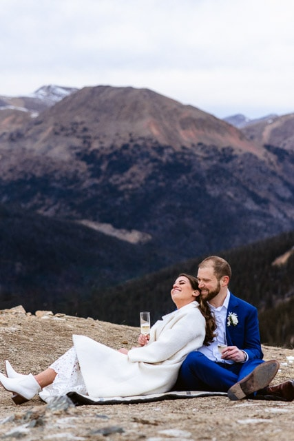 Couple enjoys a champagne toast at their adventurous Colorado elopement ceremony. Couple embraces on a mountaintop in the Rocky Mountains of Colorado during the sunset of their elopement day.