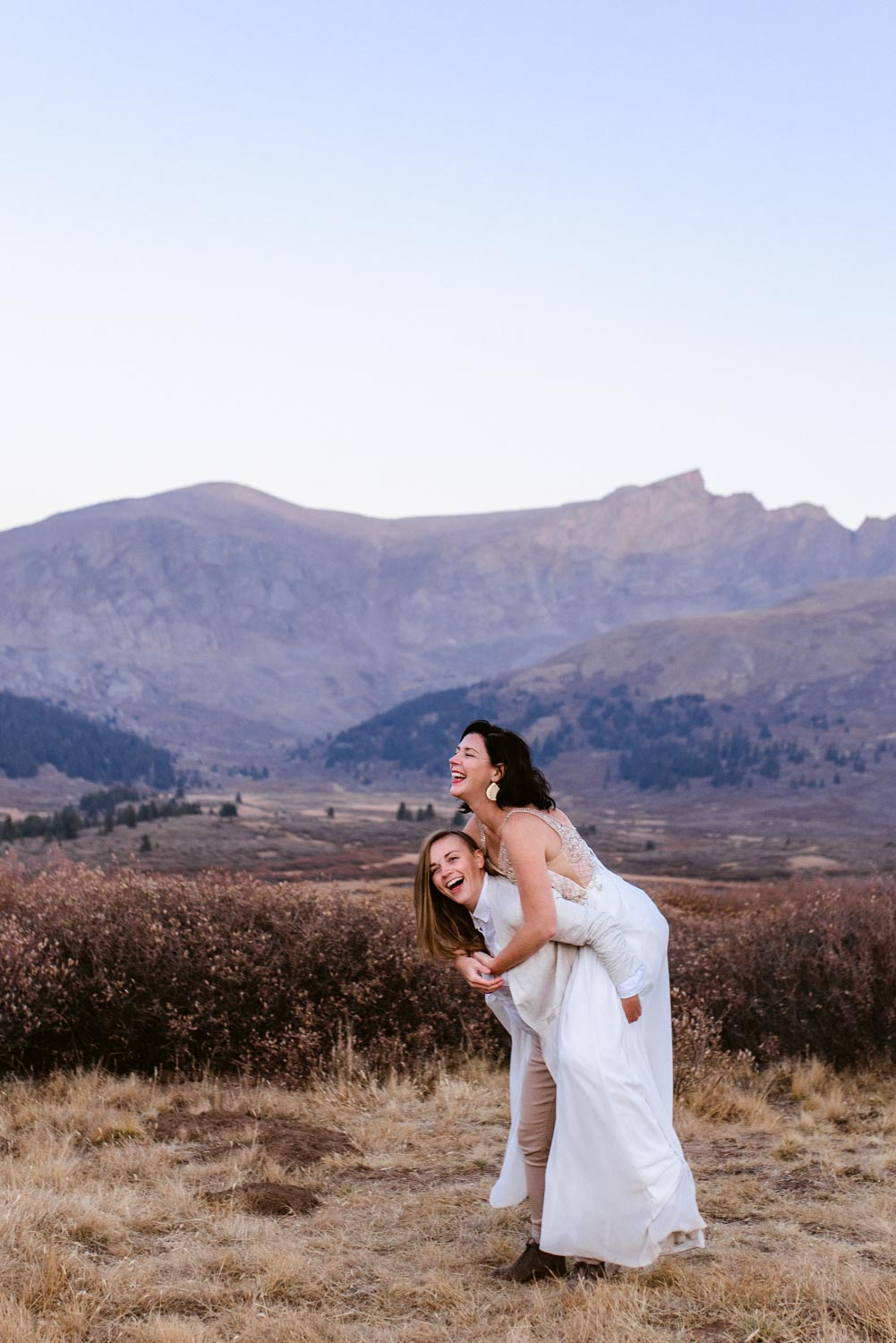A lesbian couple laughs during their elopement on top of Guanella Pass in Colorado. Guanella Pass is one of the best locations in Colorado for photographs, boasting jaw dropping mountain views and lots of Colorado color.