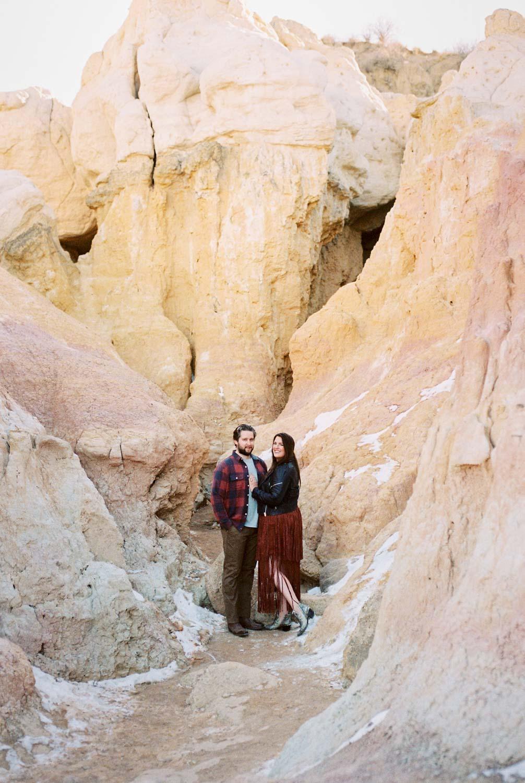 Admist the desert like landscape of Colorado's Paint Mines a couple embraces for their engagement photos. The Paint Mines near Calhan, Colorado is one of the best locations for engagement photos near Denver.