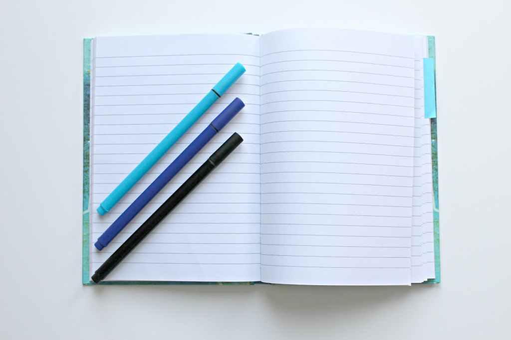 Foto de um caderno aberto com folhas em branco, e em cima dele três lápis em diagonal: o de cima azul-claro, o do meio azul-marinho e o de baixo preto, representando o propósito de estudar e aprender coisas novas. Fim da descrição.