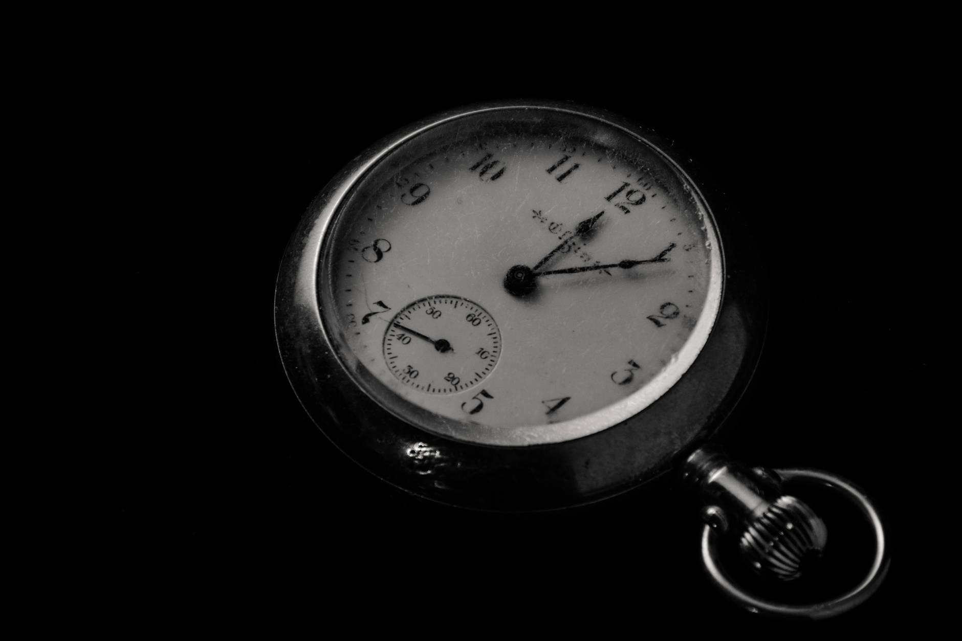 Foto de um relógio de bolso marcando meia-noite, seis minutos e quarenta e dois segundos. Fim da descrição.