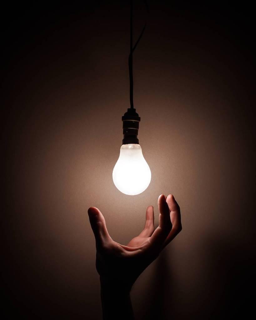 Imagem de uma lâmpada acesa com uma mão abaixo como se quisesse pegá-la. Fim da descrição.