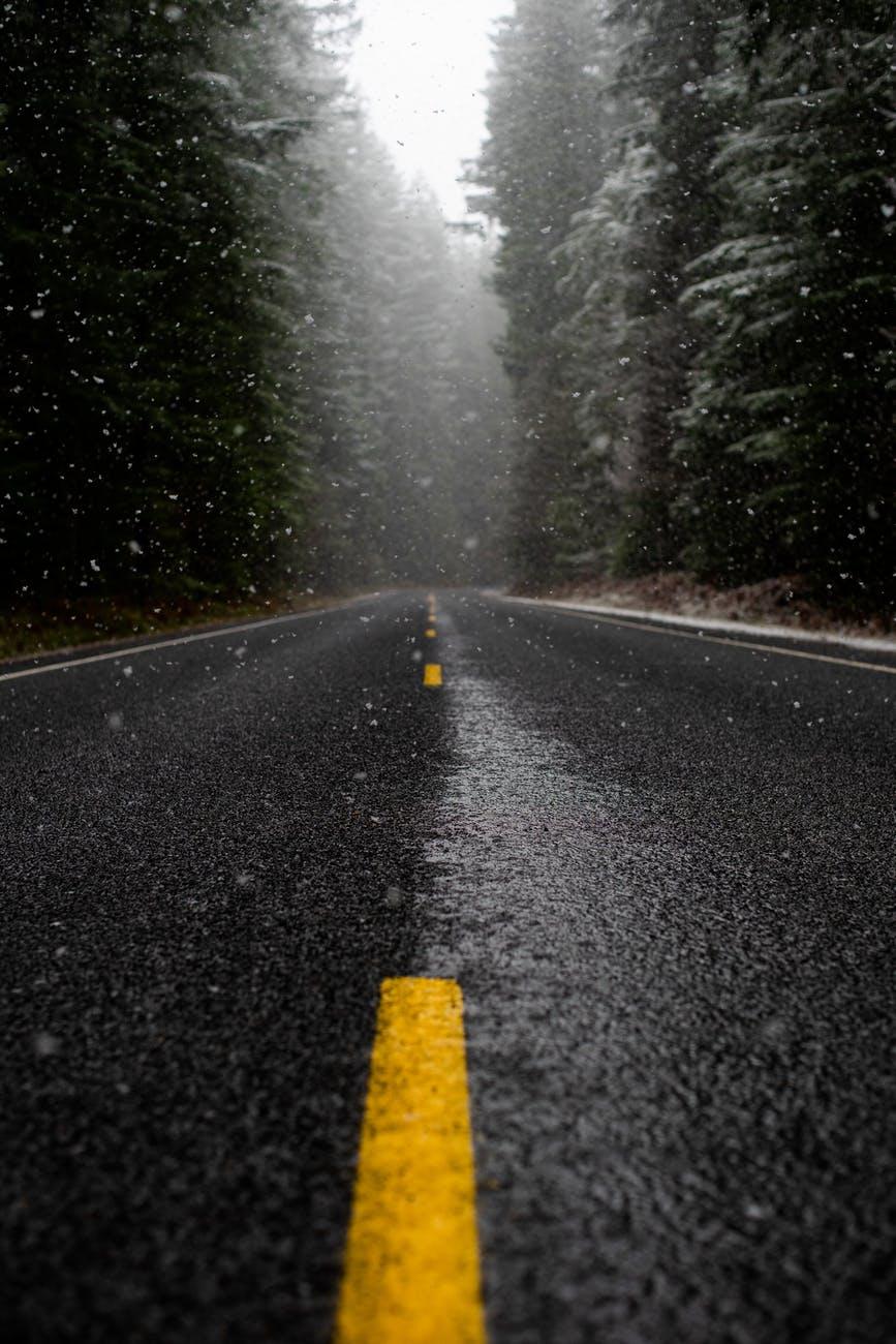 Foto de ângulo baixo de estrada enquanto chove.