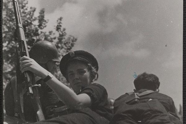 Portrait d'une jeune femme en uniforme, allongée sur un matelas, entre deux soldats. Armée, elle tourne le dos à ses compagnons et regarde le photographe. [1936-1939]. (Mémoires d'Humanité / Archives départementales de la Seine-Saint-Denis)