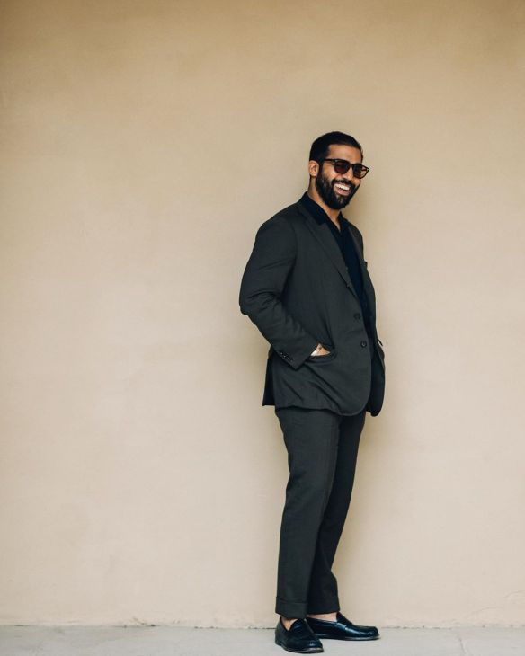 Kapil of Ring Jacket (shot by Rob Spangle) in a grey suit and black shirt and shoes.
