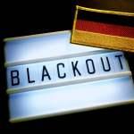 Leuchttafel mit der Aufschrift Blackout und Deutschlandfahne Symbolfoto für großflächigen Stromausf