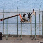 A migrant is detained by the police on a crane as he remained on top of the border fence on the wait to safely jump ont