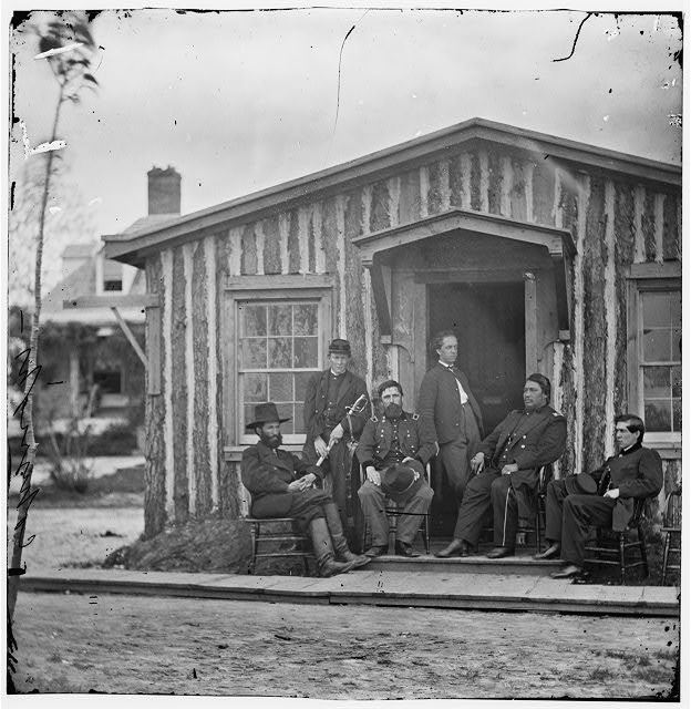 Six Union officers sitting outside a wood frame building