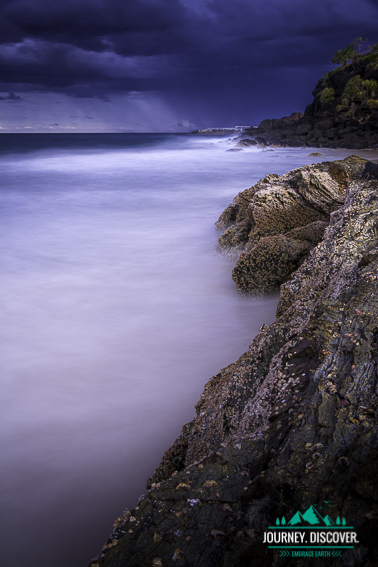 Ocean tides come up to the rocks as a dark storm broods in the background